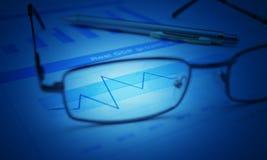 Exponeringsglas och pennan på det blåa finansiella diagrammet och grafen, blått tonar, su Arkivbild