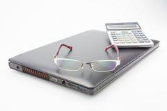 Exponeringsglas och räknemaskin på den moderna bärbara datorn Royaltyfria Foton