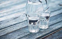 Exponeringsglas och tillbringare av kallt vatten arkivfoto