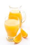 Exponeringsglas och tillbringare av orange fruktsaft och nya orange skivor Royaltyfri Foto