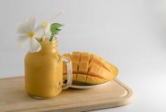 Exponeringsglas och tillbringare mycket av ny kall mangofruktsaft Arkivfoto