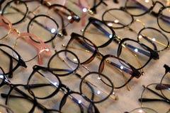 Exponeringsglas optiskt lager för glasögon, modeeyewear på nattmarknaden, färgrika exponeringsglas, exponeringsglas på hylla, exp Royaltyfria Bilder