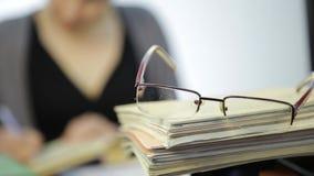 Exponeringsglas på en hög av skrivböcker, kvinna arbetar utan exponeringsglas efter visionkorrigering arkivfilmer