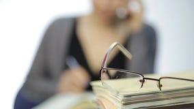 Exponeringsglas på en hög av skrivböcker, kvinna arbetar utan exponeringsglas efter visionkorrigering stock video