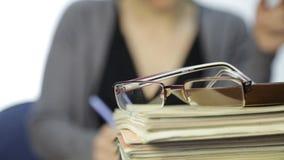 Exponeringsglas på en hög av skrivböcker och affärskvinnan med suddig fokusbakgrund arkivfilmer