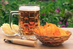 Exponeringsglas rånar av öl på trätabellen med potatischiper i vide- lodisar Royaltyfri Bild