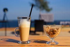 Exponeringsglas rånar med latte och den salta shaker och sockerbunken med rottingsocker på trätabellen Royaltyfri Fotografi