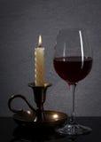 Exponeringsglas Rött vinexponeringsglas och stearinljus framme av stengranitväggen Arkivbilder