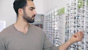 Exponeringsglas shoppar Man som försöker på glasögon i optiklager stock video