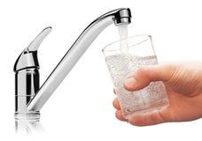 Exponeringsglas som fylls med dricksvatten från klapp. Royaltyfria Foton