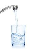 Exponeringsglas som fylls med dricksvatten från klapp. Royaltyfria Bilder