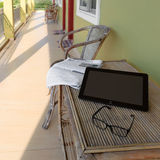Exponeringsglas, tidning och bärbar dator på trätabellen i motellbalkong Arkivbilder