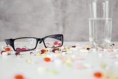 Exponeringsglas, vatten och preventivpillerar Arkivbilder
