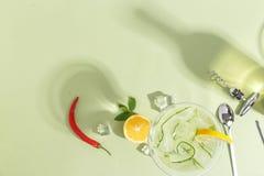 Exponeringsglasbägare med gurkavatten, en flaska och frukt på ett ljust - grön bakgrund Minimalistic idérikt begrepp kopiera avst royaltyfria bilder