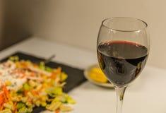 Exponeringsglaset av fint rött vin i bakgrundssalladen med bacon Royaltyfria Bilder