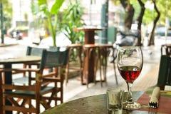 Exponeringsglaset av rött vinanseende på en tabell av gatakafét royaltyfria foton