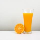 Exponeringsglaset av smaklig ren orange fruktsaft och den nya orange halvan Royaltyfri Bild