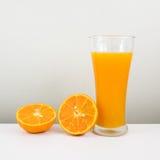 Exponeringsglaset av smaklig ren orange fruktsaft och den nya orange halvan Arkivbilder