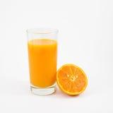 Exponeringsglaset av smaklig ren orange fruktsaft och den nya orange halvan Arkivbild