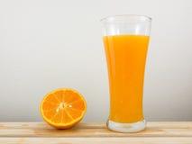 Exponeringsglaset av smaklig ren orange fruktsaft och den nya orange halvan på trämagasinet Royaltyfri Foto