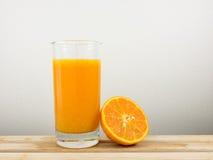 Exponeringsglaset av smaklig ren orange fruktsaft och den nya orange halvan på trämagasinet Fotografering för Bildbyråer