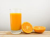 Exponeringsglaset av smaklig ren orange fruktsaft och den nya orange halvan på trämagasinet Arkivbild