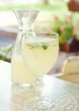 Exponeringsglaset och karaffen med en uppfriskande lemonad för sommar Arkivbilder