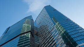 Exponeringsglasfönster av skyskrapor mot den blåa himlen royaltyfri bild