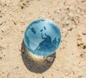 exponeringsglasjordklot på sand fotografering för bildbyråer