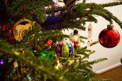 Exponeringsglasjulprydnader på ett grönt träd royaltyfria foton