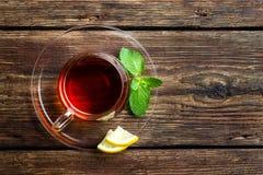 Exponeringsglaskopp med te, mintkaramellen och citronen på trälantlig bakgrund Top beskådar arkivfoto