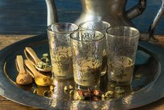 Exponeringsglaskoppar av pakistanskt te med kryddor i ett magasin och en tekanna royaltyfri bild