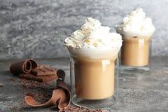 Exponeringsglaskoppar av smakligt kaffe med piskad kräm på tabellen royaltyfria bilder