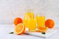 Exponeringsglaskoppar och en kanna av ny orange fruktsaft med skivor av apelsin- och gulingrör på ett ljus - grå tabell royaltyfri fotografi