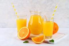 Exponeringsglaskoppar och en kanna av ny orange fruktsaft med skivor av apelsin- och gulingrör på ett ljus - grå tabell fotografering för bildbyråer
