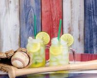 Exponeringsglaskrus fyllde med kall lemonad tillsammans med baseballsportin Royaltyfria Foton