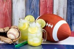 Exponeringsglaskrus fyllde med kall lemonad tillsammans med sportsliga objekt royaltyfria bilder