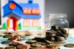 Exponeringsglaskrus med mynt och husmodell på den suddiga bakgrunden Vid ett nytt hem- begrepp royaltyfria foton