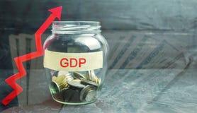 Exponeringsglaskrus med mynt och inskriften 'BNP 'och upp pil Affär som är ekonomisk, finans, lön, kris Ekonomisk tillväxtconcep arkivbild