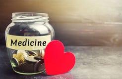 Exponeringsglaskrus med mynt och inskriften 'medicin ', Begreppet av försäkring för familjmedicin, sjukvård Medicinska kostnader  royaltyfri foto