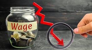Exponeringsglaskrus med mynt och ordtimpenningen och en röd ner pil Lönförminskning Droppe i vinster fallande finansiell hastighe arkivfoton