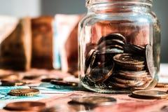 Exponeringsglaskrus med mynt på golvet av sedlar Suddiga sedlar på bakgrunden royaltyfria foton