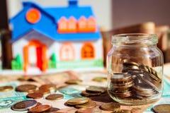 Exponeringsglaskrus med mynt på pengarfält och modell av huset på den suddiga bakgrunden Sparande pengar som köper ett husbegrepp arkivfoto