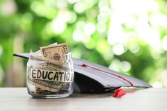 Exponeringsglaskrus med pengar och avläggande av examenhatten på tabellen mot suddig bakgrund arkivfoto