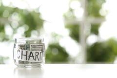 Exponeringsglaskrus med pengar och ord VÄLGÖRENHET på tabellen mot suddig bakgrund royaltyfria foton