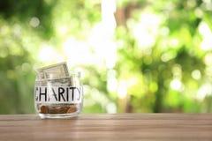 Exponeringsglaskrus med pengar och ord VÄLGÖRENHET på tabellen mot suddig bakgrund royaltyfri foto