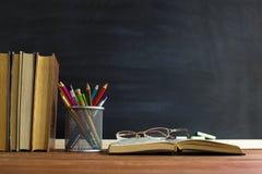 Exponeringsglasläraren bokar och en ställning med blyertspennor på tabellen, på bakgrunden av en svart tavla med krita Begreppet  arkivbild