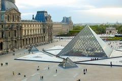 Exponeringsglaspyramid och turister som går i Louvre, karusell Arc de Triomphe, Paris, Frankrike royaltyfri fotografi