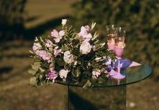 Exponeringsglastabell med blommor och exponeringsglas av champagne som står i trädgården arkivbilder