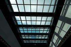Exponeringsglastak i en shoppinggalleria med en ljus sol utanför arkivbild